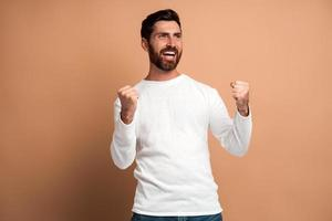 Extremely excited overjoyed man with beard making yes gesture, amazed with his victory, triumph. Indoor studio shot isolated on beige background photo