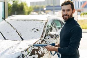 cintura para arriba retrato del hombre sonriendo a la cámara mientras sostiene un rociador de agua a alta presión para el lavado de automóviles. concepto de desinfección y limpieza antiséptica del vehículo foto