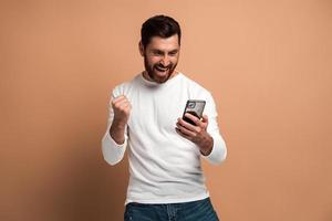 Happy overjoyed man with beard looking at the smartphone and smiling making yes gesture, celebrating victory or good deal. Indoor studio shot isolated on beige background photo