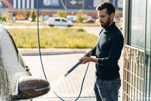 Tiro horizontal de hombre caucásico con pulverizador de alta presión con espuma de limpieza en su coche negro en el servicio de lavado de coches al aire libre. concepto de coche limpio al aire libre foto