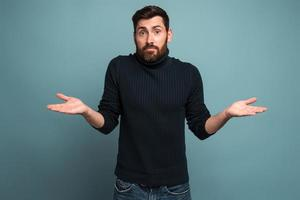 I don't know. Portrait of confused handsome bearded young man standing with raised arms and looking at camera with answer. Indoor studio shot, isolated on blue background photo