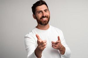 Hey you. Portrait of happy bearded man in white shirt smiling and pointing to the camera against light gray background. Studio shot photo
