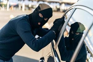 Be careful. Man dressed in black with a balaclava on his head looking at the glass of car before the stealing. Car thief, car theft concept photo