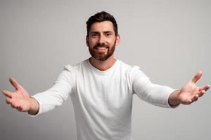 Open hearted generous man with beard sharing opening hands looking at camera with kind smile, greeting and regaling, happy glad to see you. Indoor studio shot isolated on white background photo