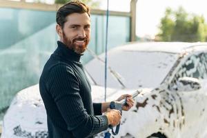 Vista vertical de cintura para arriba del hombre del placer lavando su coche en la calle con una lavadora de alta presión con espuma mientras sonríe a la cámara foto