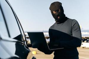 Masked thief in a balaclava stealing laptop from car and holding it opened while standing near the car. Criminal concept. Stock photo