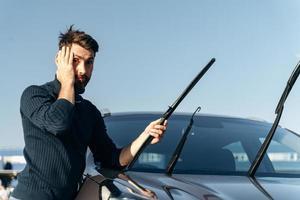 ay Dios mío. El hombre caucásico sostiene la cabeza con emociones de asombro mientras cambia los limpiaparabrisas de un automóvil. concepto de transporte foto
