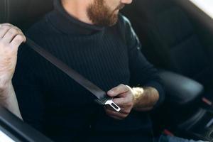 concepto de conducción segura. Hombre joven positivo abrocharse el cinturón de seguridad del coche, vista lateral, espacio de copia. alegre chico caucásico que comienza un viaje en coche, alquila un bonito y acogedor auto para viajar foto