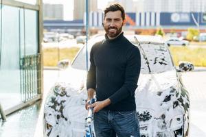 lavado de autos. limpieza del coche con agua a alta presión. lavado de autos en el lugar especial solo. Hombre sonriendo a la cámara mientras lava el coche negro foto