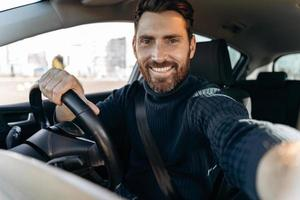 Great selfie. Handsome bearded man holding camera and making selfie while sitting in the car at the driver seat and looking at the camera with pleasure smile photo