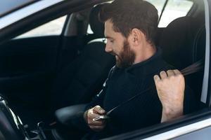 Vista lateral del joven barbudo caucásico en un coche abrochándose los cinturones de seguridad antes de conducir. chico seguro de montar en el trabajo. foto de stock