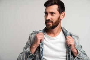Portrait of bearded handsome man in casual style looking away and smiling while straightening his clothes and posing to the camera. Studio shot on white background photo