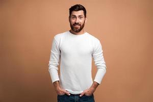 Retrato de brutal guapo joven barbudo modelo en camisa blanca de pie y mirando a la cámara con cara orgullosa de placer. Foto de estudio de interior aislado sobre fondo beige