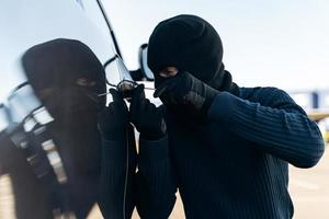 Close up view of the dangerous man dressed in black with a balaclava on his head preparing breaking with crowbar the glass of car before the stealing. Car thief, car theft concept photo