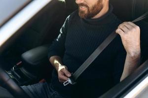 Vista de cerca del joven barbudo caucásico en un coche abrochándose los cinturones de seguridad antes de conducir. chico seguro de montar en el trabajo. foto de stock