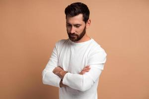 Retrato de un joven barbudo pensativo guapo de pie con los brazos cruzados y mirando hacia abajo con expresión reflexiva mientras posa frente a la cámara sobre fondo beige foto