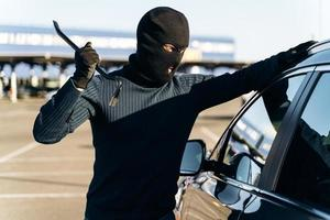 Dangerous man dressed in black with a balaclava on his head preparing breaking with crowbar the glass of car before the stealing. Car thief, car theft concept photo