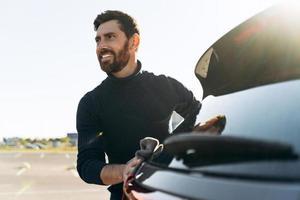 Cintura para arriba retrato de un joven hombre caucásico limpiando su coche con una microfibra al aire libre al atardecer mientras mira a alguien en la calle foto