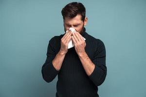 resfriado y gripe. retrato de un joven barbudo enfermo de pie, sosteniendo un pañuelo en la boca y sintiendo tristeza y enfermedad. Foto de estudio de interior, aislado sobre fondo azul.