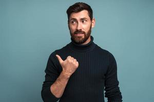 Portrait of happy excited man with beard pointing side with his finger, find out solution or idea, get answer on question, eureka. Indoor studio shot isolated on blue background photo