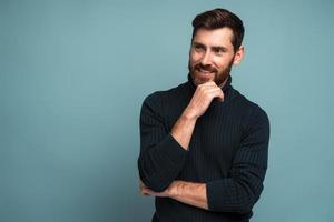 Portrait of cheerful unshaven man standing with hand near his face and smiling while looking away. Male appearance concept. Indoor studio shot isolated on blue photo