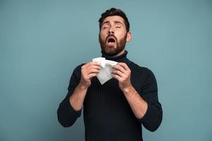toser o estornudar. hombre enfermo estornuda tejido, tos, malestar, malestar o gripe, alergia o síntomas de gripe estacional. Foto de estudio de interior aislado sobre fondo azul.