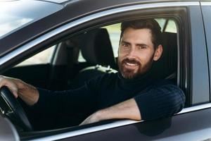 Happy caucasian man sitting and looking at the window while having long road by the car. Busy people and transportation concept photo