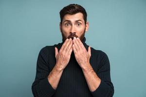 Shocked man closing mouth with hands, confused and depressed with information, looking with astonishment and fear, privacy. Indoor studio shot isolated on blue background photo