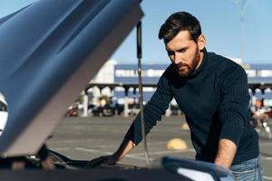 Upset bearded man checking his car engine after breaking down on the road. Serious male is standing in front of the opening hood. Transportation concept photo