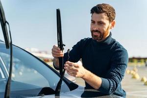 propietario de automóvil masculino comprobando el limpiaparabrisas en la calle. El hombre está cambiando los limpiaparabrisas de un automóvil. concepto de reparación de automóviles foto
