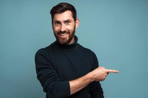 Advertise here. Positive bearded man pointing finger away paying your attention at empty space for advertisement, looking at camera with toothy smile. Indoor studio shot isolated on blue background photo