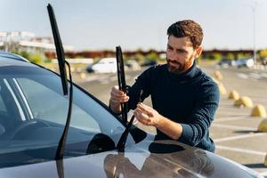 Man is changing windscreen wipers on a car while standing at the street. Male replace windshield wipers on car. Change cars wiper blades concept photo