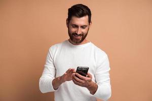 Hombre barbudo asertivo mirando atentamente la pantalla del teléfono inteligente que sostiene, navegando por internet, haciendo compras en línea. Foto de estudio de interior aislado sobre fondo beige