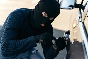 Close up view of the dangerous man dressed in black with a balaclava on his head picks the lock with a pick while stealing. Car thief, car theft concept photo