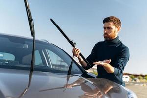 Hombre caucásico que se siente confundido mientras cambia los limpiaparabrisas de un automóvil en la calle durante el día soleado. concepto de transporte foto