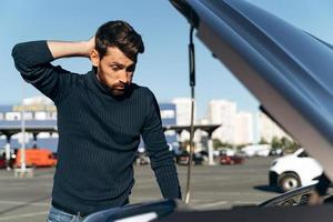 Bewildered man looking at the engine room of his car seems to have an abnormal condition. Guy thinking what to do. Concept about car insurance photo