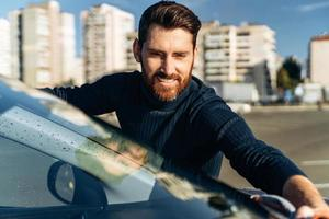 Smiling man cleaning car and drying vehicle with microfiber cloth. Hand wipe down paint surface of shiny car after polishing. Car detailing and car wash concept photo