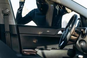 View from the car at the man dressed in black with a balaclava on his head preparing breaking with crowbar the glass of car before the stealing. Car thief, car theft concept photo