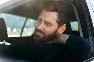 Tired businessman in car feeling strong neck pain and nerve inflammation, after long road. Transportation and health problems concept photo