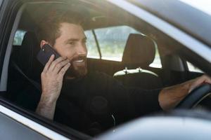 en la carretera. Vista vertical del hombre caucásico consciente mirando por la ventana mientras charla a través del teléfono inteligente con su colega durante el largo camino hacia el trabajo foto