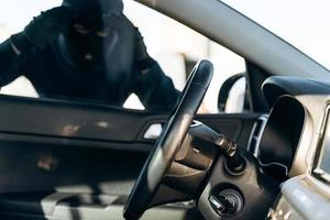 View from the car at the man dressed in black with a balaclava on his head looking at the glass of car before the stealing. Car thief, car theft concept photo