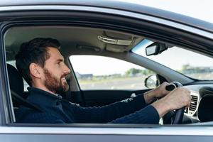 Side view of the handsome businessman driving car before buying. Attractive elegant man in business closes driving car. Transportation concept photo