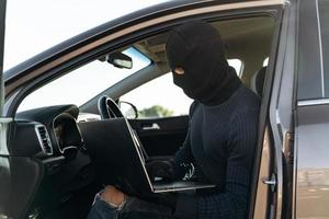Masked thief in a balaclava stealing laptop from car and looking at the screen while sitting inside. Criminal concept. Stock photo