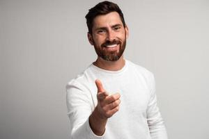 Extremely happy bearded man laughing and pointing finger at you looking at camera, funny ridiculous joke. Indoor studio shot isolated on white background photo