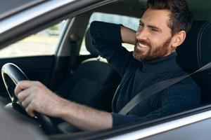 View from the street of the young man rubbing his aching neck, while looking tired from driving. Male driver having neck pain, sitting in his car photo