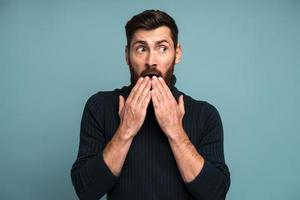 Wow. Man covering mouth with hand and looking away with big eyes, scared surprised expression, shocked by sudden news. Indoor studio shot isolated on blue background photo