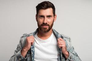 Portrait of bearded handsome man in casual clothes looking at the camera and smiling while correcting his jacket and posing. Studio shot on white background photo