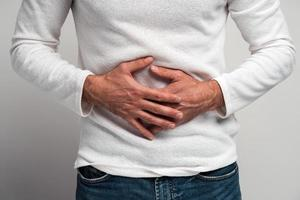 Close up view of the man holding hands on stomach feeling acute pain, suffering indigestion and nausea, duodenal ulcer. Indoor studio shot isolated on white background photo