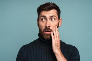 Excited shocked man holding hands on face and looking away with big eyes and open mouth, shocked bemused with news, win at lottery. Indoor studio shot isolated on blue background photo