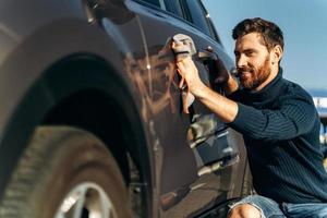 Man wiping his car at the street. Close up view of the handsome bearded man in casual wear washing car doors and hood with microfiber cloth. Car detailing wash during the sunny day concept photo